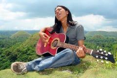 Adolescente asiático con la guitarra Foto de archivo libre de regalías