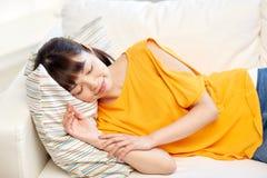Adolescente asiático feliz que dorme no sofá em casa Imagens de Stock Royalty Free