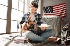 Adolescente asombroso que celebra con su perro Imagenes de archivo