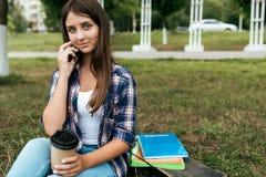 Adolescente astuto della ragazza 11-12 anni, sedentesi di estate nel parco della città Sorrisi felici, chiamate su Internet Vicin fotografia stock libera da diritti