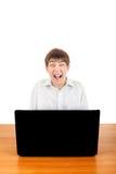 Adolescente asustado detrás del ordenador portátil Imagen de archivo libre de regalías