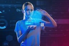 Adolescente atento que sostiene un smartphone y que hace un holograma Imagen de archivo