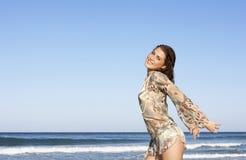 Adolescente atractivo con la presentación extendida de los brazos por el mar Foto de archivo libre de regalías
