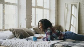 Adolescente atractivo de la raza mixta lauging usando el ordenador portátil para compartir los medios sociales que mienten en cam Fotos de archivo libres de regalías