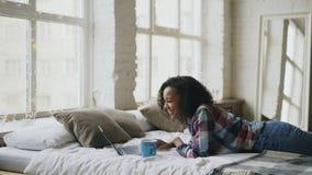 Adolescente atractivo de la raza mixta lauging usando el ordenador portátil para compartir los medios sociales que mienten en cam Imagen de archivo libre de regalías