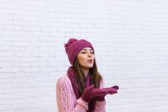 Adolescente atractivo de la sonrisa en espacio de la copia del beso del sombrero que sopla rosado Foto de archivo