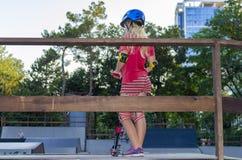 Adolescente atractivo en llevar a cabo a su tablero patinador brillante en skatepark Imagen de archivo
