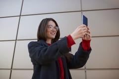 Adolescente atractivo en ropa de sport y vidrios elegantes usando el dispositivo digital moderno Imagen de archivo libre de regalías