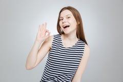 Adolescente atractivo feliz en el top rayado que muestra la muestra aceptable Imagen de archivo libre de regalías