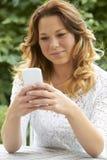 Adolescente atractivo que envía el mensaje de texto en el teléfono Foto de archivo