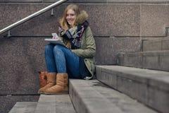 Adolescente atractivo que se sienta en pasos en ciudad Foto de archivo