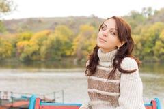 Adolescente atractivo que se sienta en un lago Foto de archivo libre de regalías