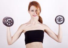 Adolescente atractivo que trabaja-hacia fuera con pesas de gimnasia Foto de archivo