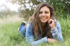 Adolescente atractivo sonriente con el pelo largo al aire libre Imagenes de archivo