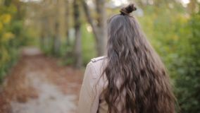 Adolescente atrativo n da menina com um livro que fala no telefone celular ao andar no parque bonito do outono Menina feliz vídeos de arquivo