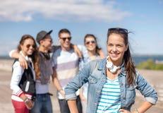 Adolescente avec des écouteurs et des amis dehors Images libres de droits