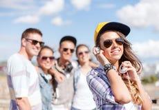 Adolescente avec des écouteurs et des amis dehors Photos stock