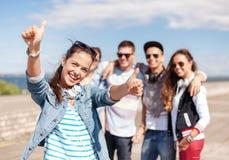 Adolescente avec des écouteurs et des amis dehors Photos libres de droits