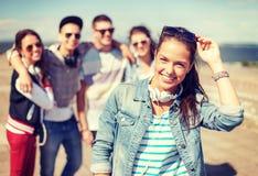 Adolescente avec des écouteurs et des amis dehors Image stock
