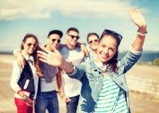 Adolescente avec des écouteurs et des amis dehors Photo stock