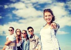 Adolescente avec des écouteurs et des amis dehors Photographie stock