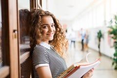 Adolescente avec des carnets dans le hall de lycée pendant la coupure Photographie stock
