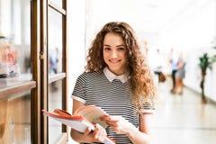 Adolescente avec des carnets dans le hall de lycée pendant la coupure Photos libres de droits