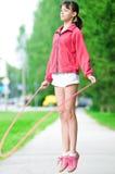 Adolescente avec la corde à sauter au stationnement Photographie stock libre de droits