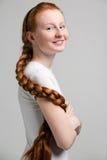 Adolescente avec la longue tresse rouge Images stock