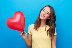 Adolescente avec le ballon en forme de coeur rouge image libre de droits