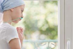 Adolescente avec le cancer de poumon regardant par la fenêtre au centre médical image stock