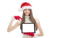 Adolescente avec le chapeau de Santa montrant l'écran de tablette Photographie stock libre de droits