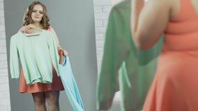 Adolescente avec le poids supplémentaire sélectionnant le nouvel équipement devant le miroir de plein-taille banque de vidéos