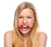 Adolescente avec le poivre de piment rouge dans la bouche Photographie stock