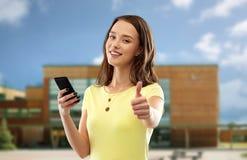 Adolescente avec le smartphone montrant des pouces  photographie stock