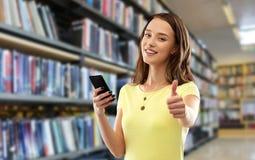 Adolescente avec le smartphone montrant des pouces  images stock