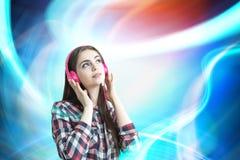 Adolescente avec les écouteurs roses, couleurs Photos libres de droits