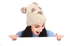 Adolescente avec un chapeau se cachant derrière un panneau-réclame Images stock