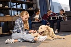 Adolescente ayant l'amusement avec le chien de golden retriever tandis qu'amis s'asseyant sur le sofa Photographie stock libre de droits