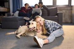 Adolescente ayant l'amusement avec le chien de golden retriever tandis qu'amis s'asseyant sur le sofa Photographie stock
