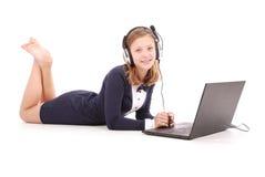 Adolescente bastante joven con el ordenador portátil y los auriculares que mienten en el piso Foto de archivo libre de regalías