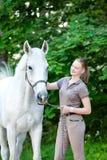 Adolescente bastante joven que rasguña el cuello del ` s del caballo blanco Fotografía de archivo libre de regalías