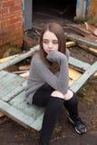 Adolescente bastante joven que se sienta en algunas puertas viejas Imagen de archivo libre de regalías