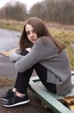 Adolescente bastante joven que se sienta en algunas puertas viejas al aire libre Fotografía de archivo