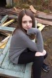 Adolescente bastante joven que se sienta en algunas puertas viejas al aire libre Fotografía de archivo libre de regalías