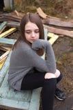 Adolescente bastante joven que se sienta en algunas puertas viejas al aire libre Imágenes de archivo libres de regalías