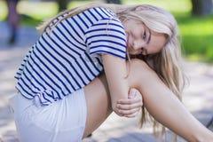 Adolescente bastante rubio en la camisa rayada que presenta con sonrisa Foto de archivo