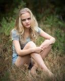 Adolescente bastante rubio que se sienta en la hierba Imagenes de archivo