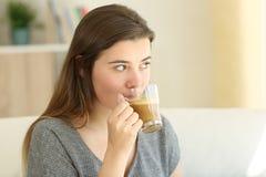 Adolescente bebiendo un café con la leche que mira lejos en casa Imagenes de archivo