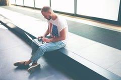 Adolescente bello che studia sul suo computer portatile mentre sedendosi nel corridoio dell'università Immagine Stock
